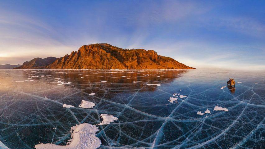 Luftaufnahme eines Autos bei der Fahrt über den zugefrorenen Baikalsee, Russland